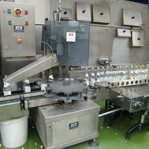 Bevor die Mehrwegflaschen gewaschen werden können, wird der alte Verschluß maschinell entfernt.