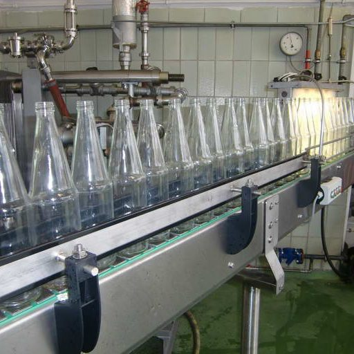 Von der Waschmaschine aus, gelangen die die Flaschen auf schnellstem Wege zum befüllen. Im Hintergrund erkennt man wieder den Plattenwärmeübertrager, von wo aus der pasteurisierte Saft direkt zur Füllmaschine gelangt.