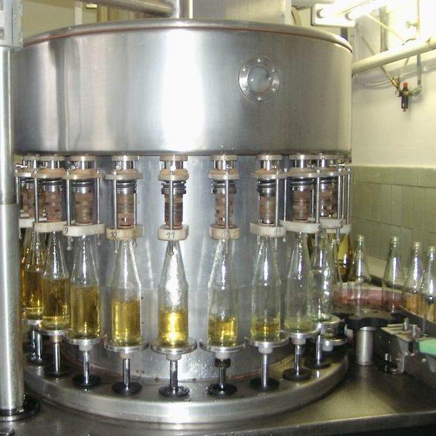 Die Flaschen werden nun in einem Vakuumfüller randvoll befüllt.
