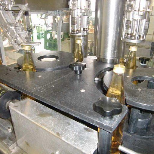 Unmittelbar nach dem Füllvorgang werden die Flaschen verschlossen. Dabei wird zunächst eine gewindelose Kapsel auf die Flaschenmündung gesetzt und anschließend das Gewinde eingerollt.