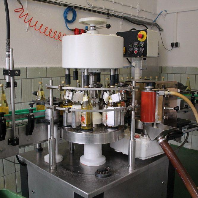 Nachdem die verschlossenen Flaschen außen nochmals gespült wurden, werden sie etikettiert und automatisch das Mindesthaltbarkeitsdatum aufgedruckt.